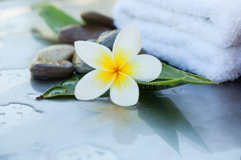 Tropikalny kwiat z ręcznikiem i kamieniami zdjęcie royalty free