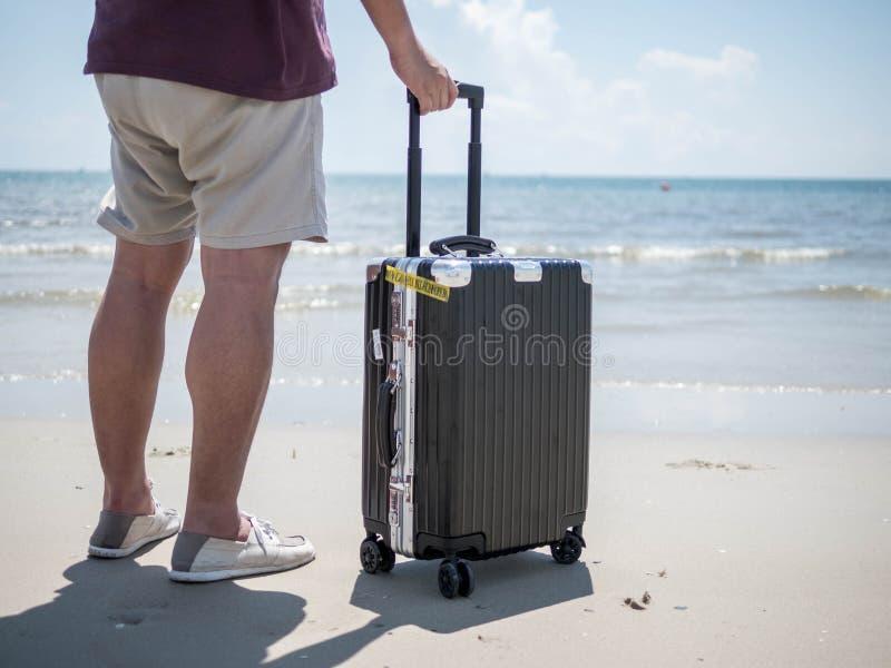 Tropikalny morze, młody człowiek pozycja z podróży walizką przy plażą Wakacje letni pojęcia projekta podróżny sztandar z copyspac obraz stock