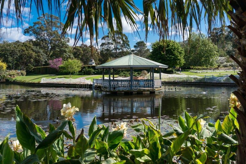 Tropikalny park z summerhouse blisko zielonych drzew i stawu bujny kwiat?w i obraz royalty free