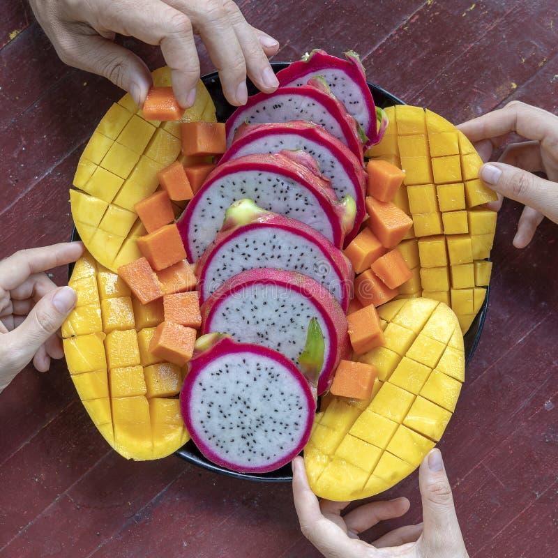 Tropikalnych owoc asortyment na talerzu i ludziach ręk, zakończenie w górę Yummy deser, zakończenie w górę Mango, melonowiec, pit fotografia royalty free