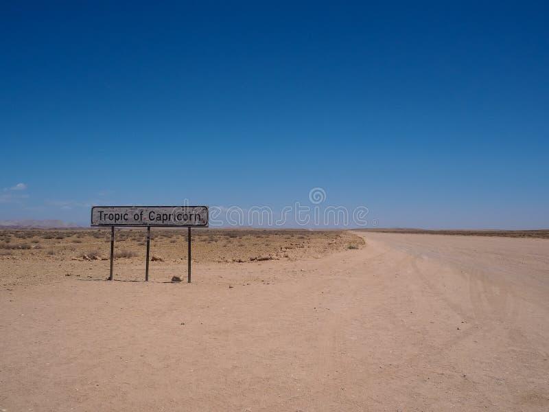 Tropique de ligne signage de Capricorne le long de la route de désert avec le bleu photographie stock