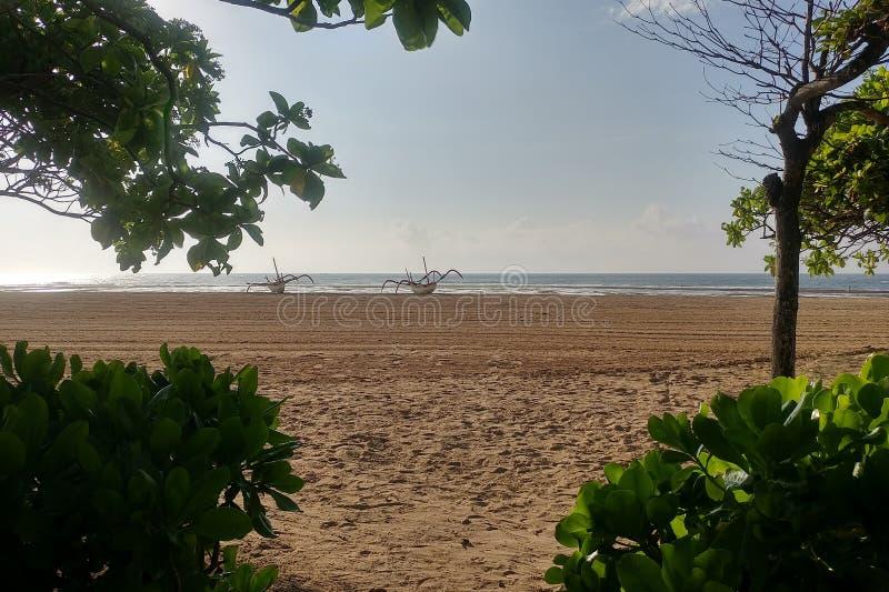 tropiques Plage sablonneuse large à marée basse Les bateaux de pêche traditionnels se tiennent sur seul le sable photographie stock libre de droits
