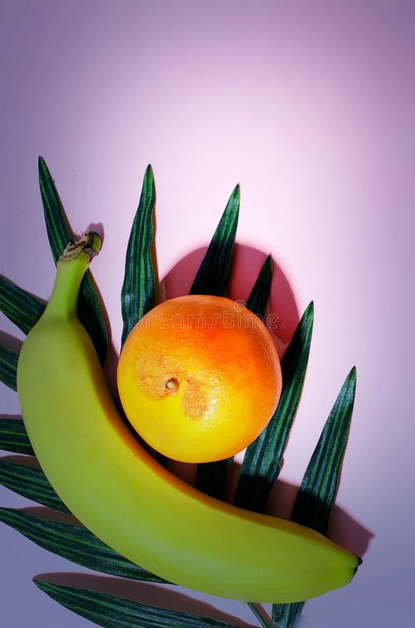 Tropisch fruit, een banaan en een sinaasappel, die op een varenblad van de zijdepalm met een kleurrijke achtergrond leggen royalty-vrije stock afbeelding