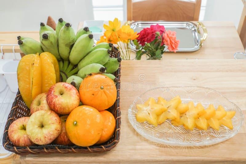 Tropisch fruit van banaan, sinaasappel, starfruit op houten lijst in keuken royalty-vrije stock afbeeldingen