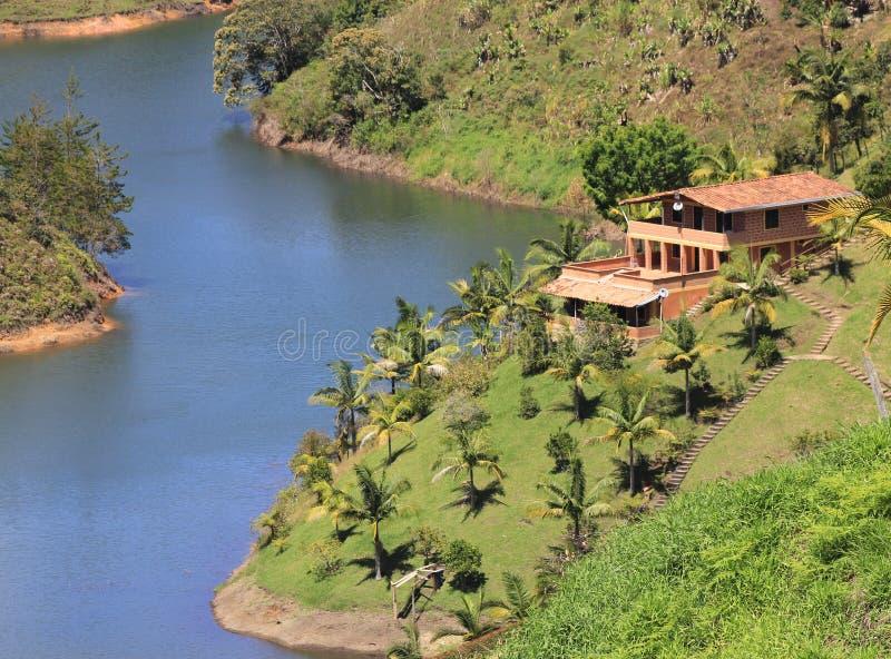 Tropisch herenhuis op een rivier stock afbeelding
