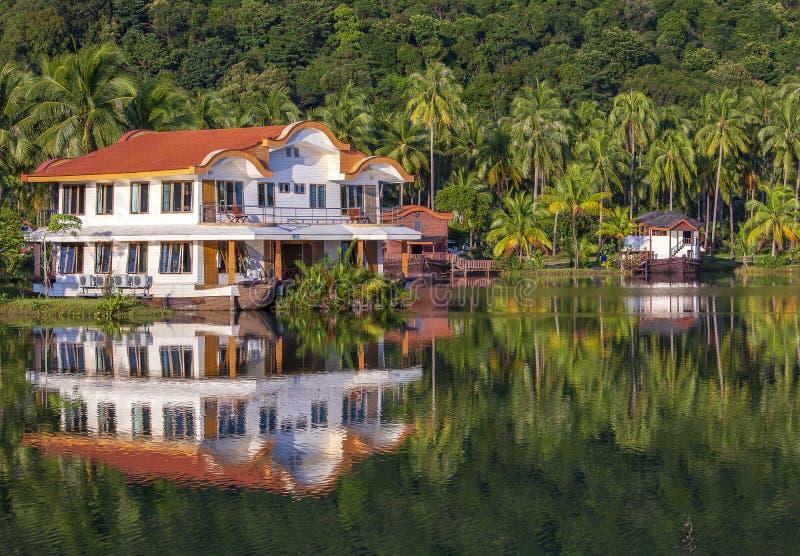 Tropisch huis in de vorm van een schip naast het overzees in de wildernis met groene palmen De toevlucht van het luxestrand op ee royalty-vrije stock afbeelding