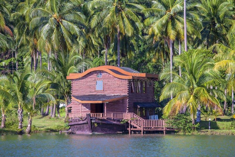 Tropisch huis in de vorm van een schip naast het overzees in de wildernis met groene palmen De toevlucht van het luxestrand op ee royalty-vrije stock foto