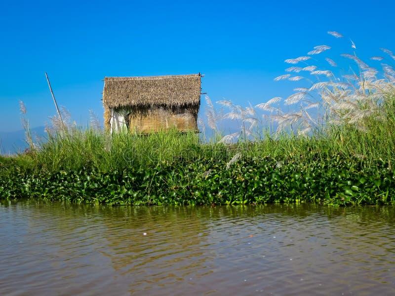 Tropisch huis langs vreedzaam meer stock fotografie