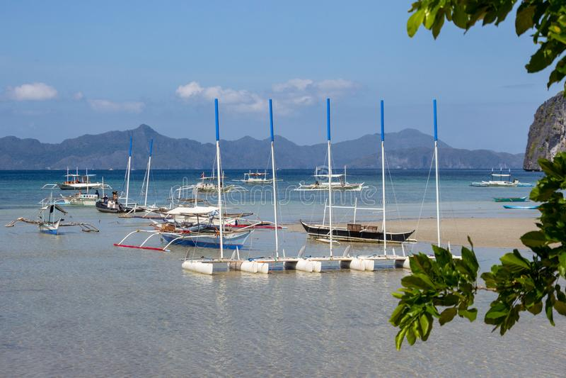 Tropisch landschap met traditionele Pilippines-boten De lagune van het Palawaneiland met bergen op horizon stock foto's