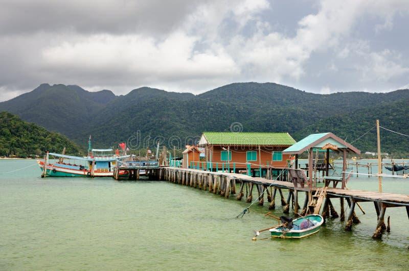Tropisch landschap met turkooise tropische overzees, vissersboot, huis op het water, houten pijler en Koh Chang-eiland op horizon royalty-vrije stock afbeelding