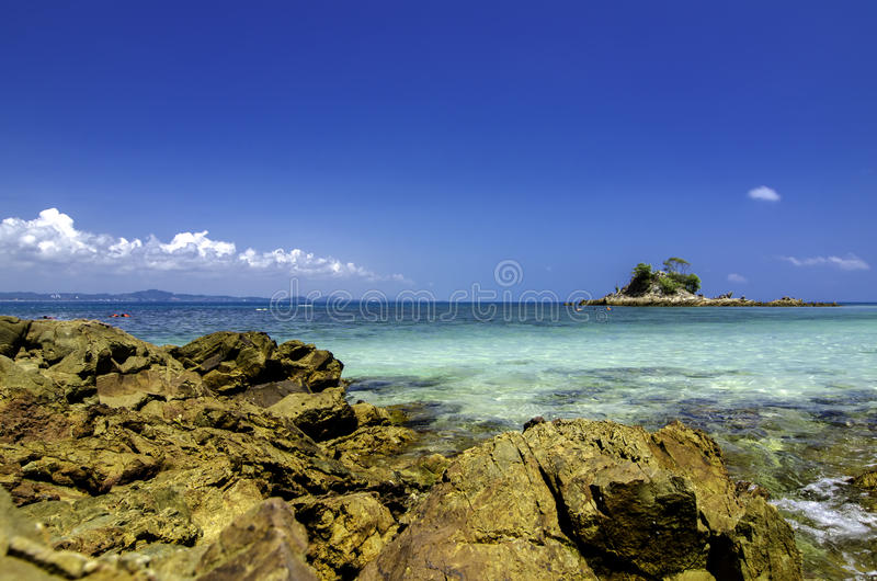 Tropisch strand bij Kapas-Eiland, Maleisië Natte Rots en glashelder zeewater met blauwe hemelachtergrond royalty-vrije stock afbeeldingen