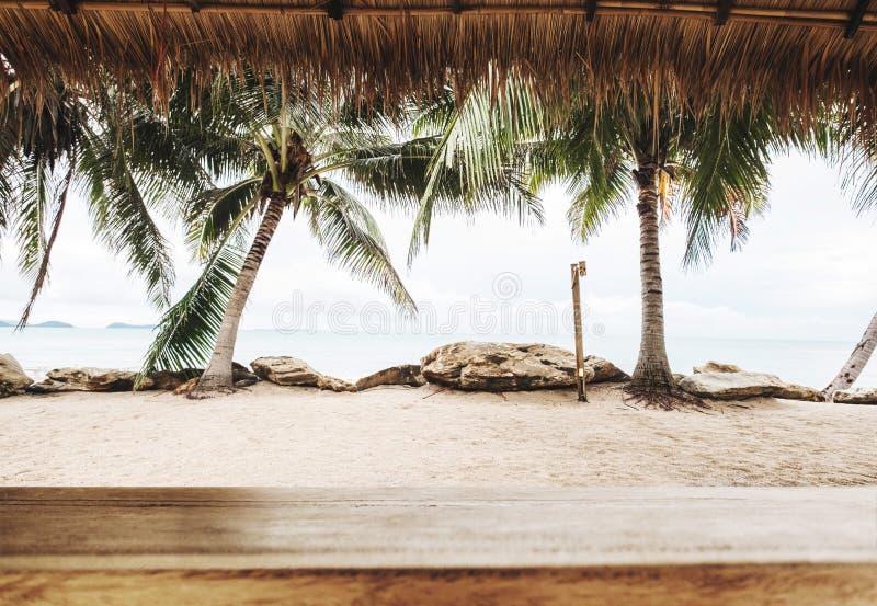 Tropisch strand in de zomer, houten lijstbovenkant met vage kokospalmen, zand en de strandachtergrond stock afbeelding