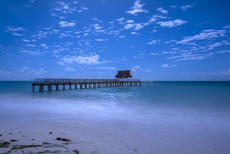 Tropisch strand en dok bij nacht stock afbeelding