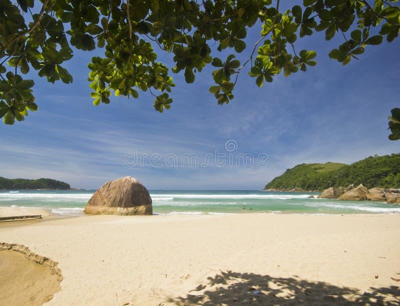 Tropisch strand met blauw water en grote steen op kust royalty-vrije stock afbeeldingen