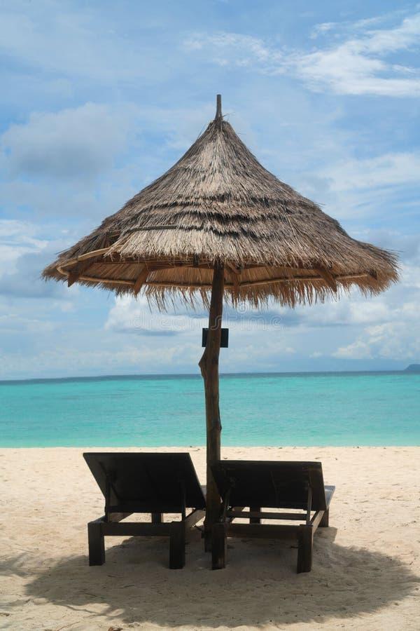 Tropisch strand met deckchairs en paraplu over lagunezeewater royalty-vrije stock afbeeldingen