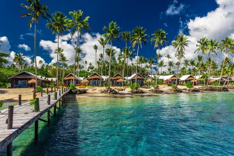 Tropisch strand met met kokosnotenpalmen en villa's op Samoa stock afbeeldingen