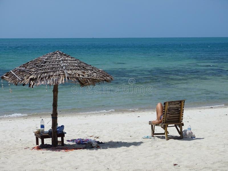 Tropisch strand met wit zand, blauwe water en parasol royalty-vrije stock afbeelding