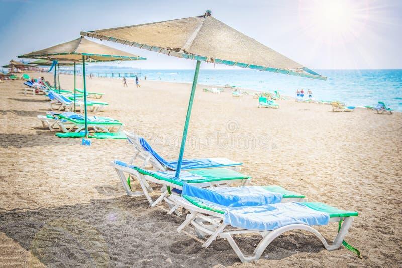 Tropisch toevlucht overzees strand Paraplu's en chaise zitkamers dichtbij overzees op zandig strand Ontspan en rust op strand stock afbeelding