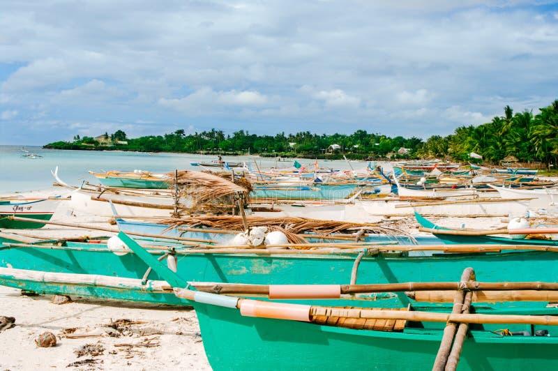 Tropisch wit zandstrand met groene palmen en geparkeerde vissersboten in het zand Exotisch eilandparadijs stock fotografie