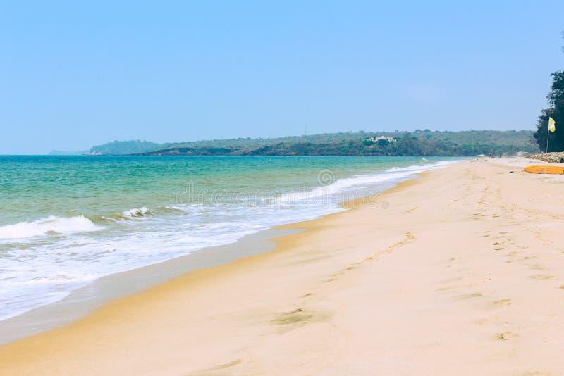 Tropisch zandig strand van het overzees met golven en zonnige hemel stock afbeelding
