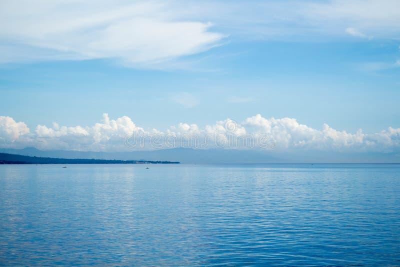 Tropisch zeegezicht met ver eiland en blauwe hemel Ontspannende overzeese mening met nog zeewater royalty-vrije stock afbeeldingen