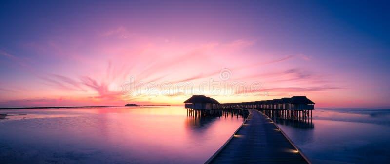 Tropisch zonsondergangpanorama Strandzonsondergang in het eiland van de Maldiven met de villa's van het luxewater en lange houten stock foto