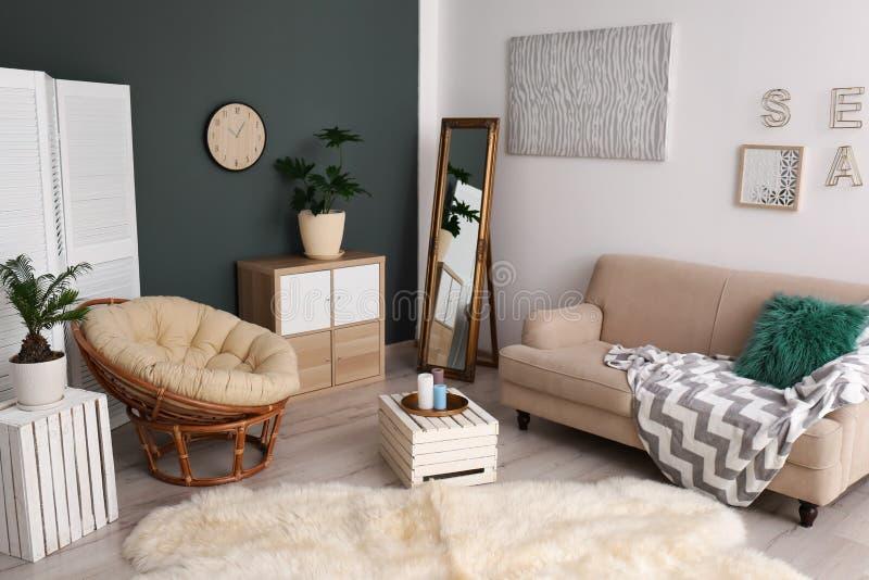 Tropische Anlagen mit grünen Blättern und bequemen Möbeln lizenzfreies stockbild