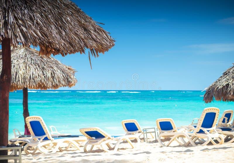 Tropische Ansicht eines Strandes mit Regenschirmen und Strandstühlen stockfotos