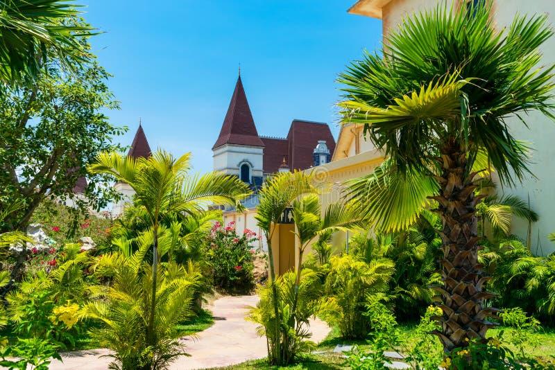 Tropische Bäume und Blumen im schönen Park an einem sonnigen Tag mit Schlossdach stockfoto
