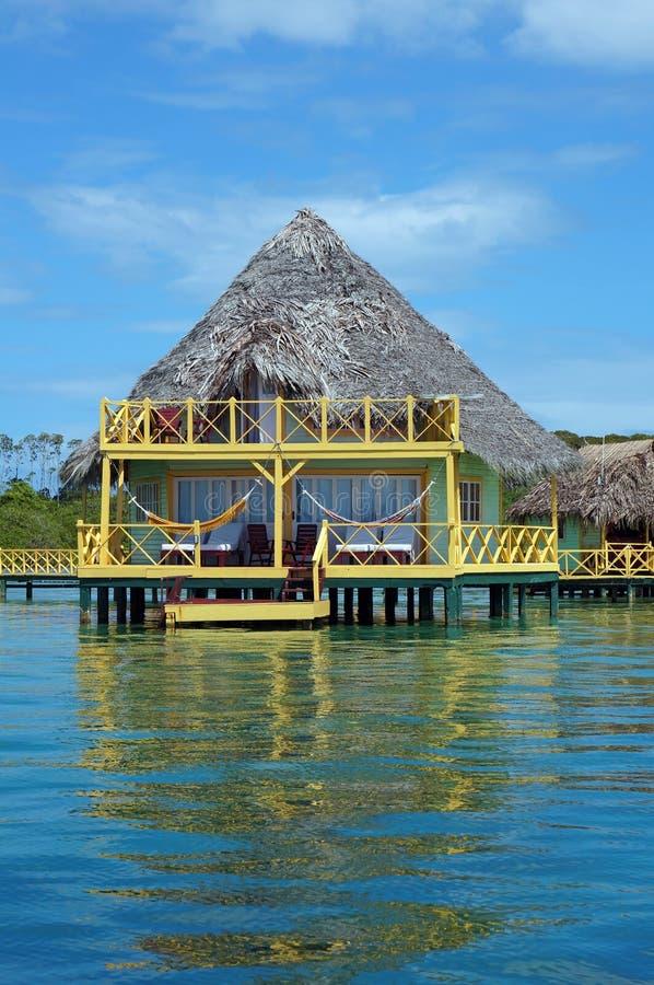 Tropische bungalow over water met met stro bedekt dak stock afbeelding