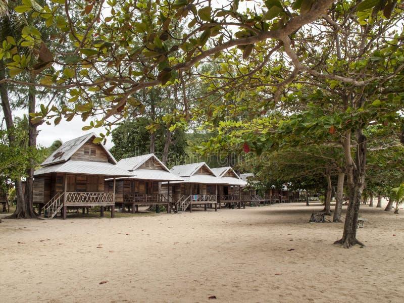 Tropische Bungalows angeschmiegt unter Bäumen lizenzfreie stockfotos
