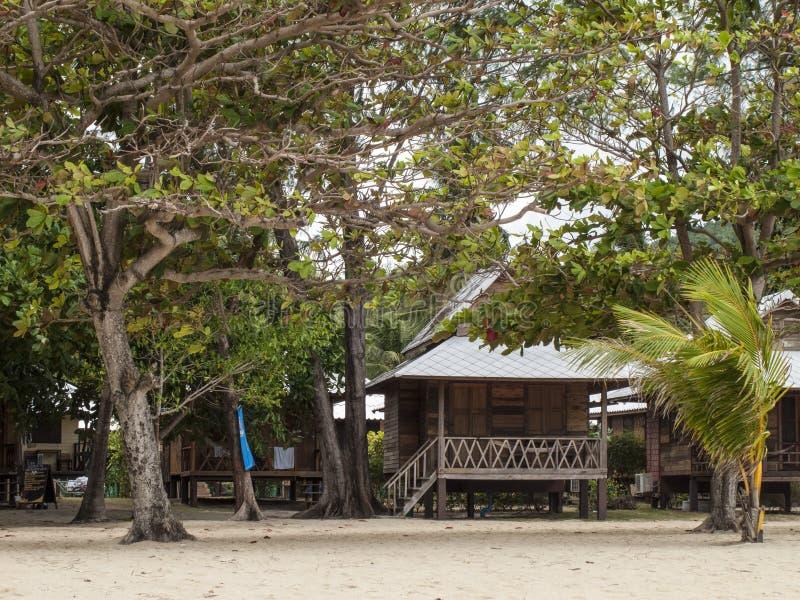Tropische Bungalows unter Bäumen lizenzfreie stockfotos