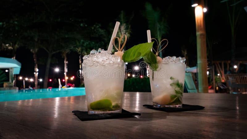Tropische cocktails met veel ijs door een aangestoken pool bij nacht royalty-vrije stock foto
