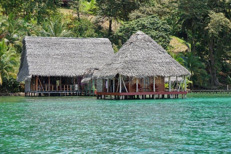 Tropische ecolodge over water met met stro bedekt dak stock afbeeldingen
