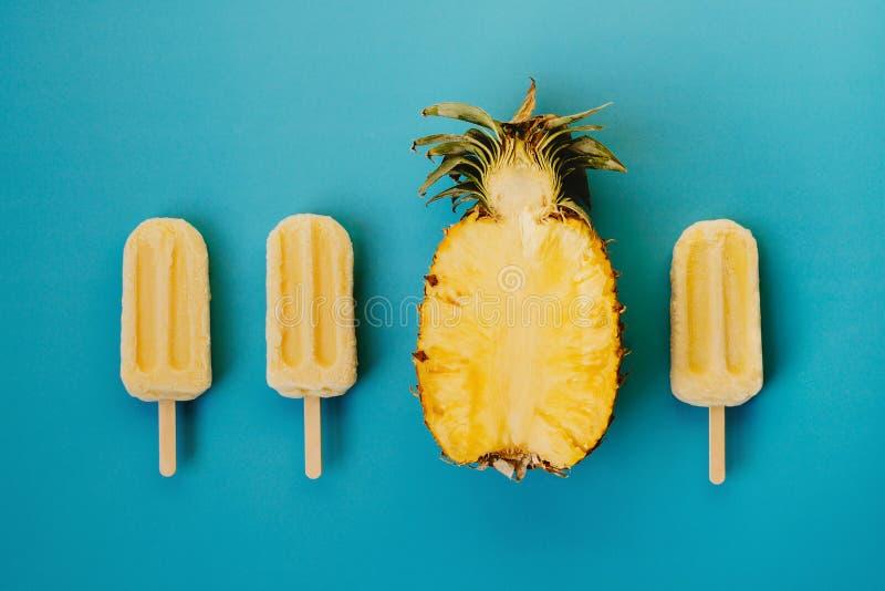 Tropische flache Lage des Eises am Stiel drei strengen Vegetariers und Hälfte der reifen Ananas lizenzfreie stockbilder