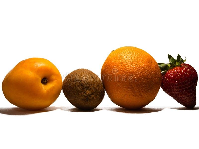 Tropische Früchte: Aprikose, Kiwi, Orange und Erdbeere auf weißem Hintergrund mit Kopienraum stockfotografie