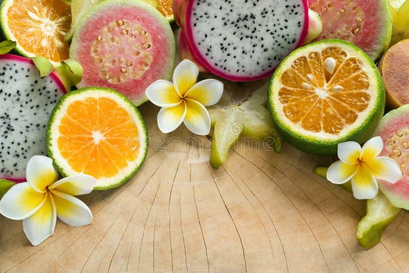 Tropische Früchte Tangerine, Guave, Drachefrucht, Sternfrucht, Sapotillbaum mit Blumen von Plumeria auf dem hölzernen Hintergrund lizenzfreie stockfotos