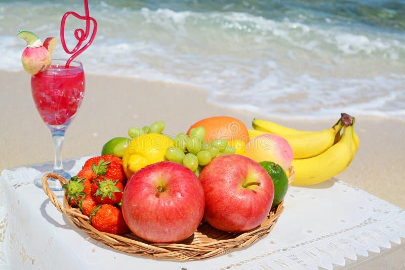 Tropische Früchte und Getränk auf dem Strand stockfoto