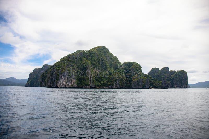 Tropische kust met nog zeewater en verlaten eiland Zwart rotsen ith groen bos in overzees Natuurlijk landschap royalty-vrije stock fotografie