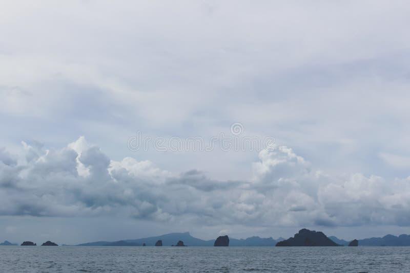 Tropische kust met wolken en bergen stock foto's