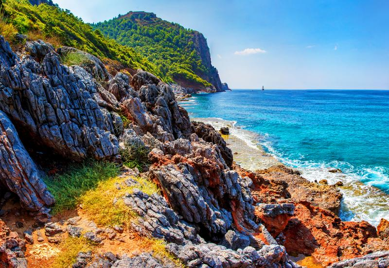 Tropische Landschaft der felsigen Küstenlinie mit Bergen und blauem Meerwasser am klaren sonnigen Sommertag stockfotografie