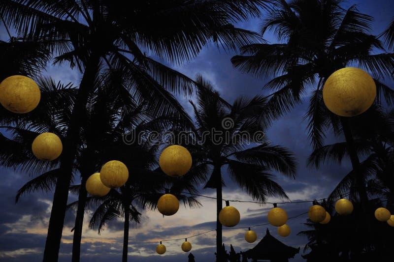 Tropische Nachtlandschaft am Luxusstrandurlaubsort mit Blick auf Palmen unter einem Sonnenunterganghimmel mit Lampen und Laterne  lizenzfreies stockbild