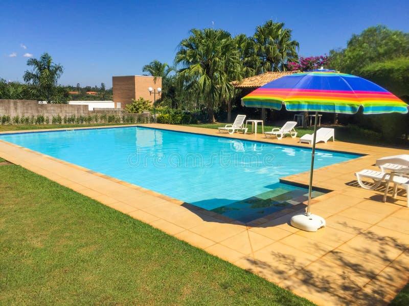 Tropische pool met palmen en zonschaduw stock foto's