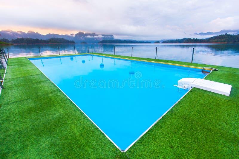 Tropische Rücksortierung Poolside mit schönem Seeblick lizenzfreies stockbild