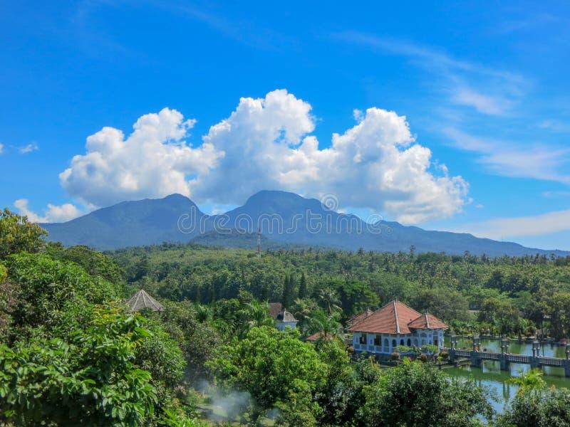 Tropische siertuin met groot zwembad Bezinning over waterspiegel Op de achtergrond de bergen van Lempuyang stock fotografie