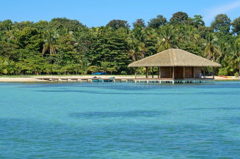 Tropische strand en bungalow over water stock afbeeldingen
