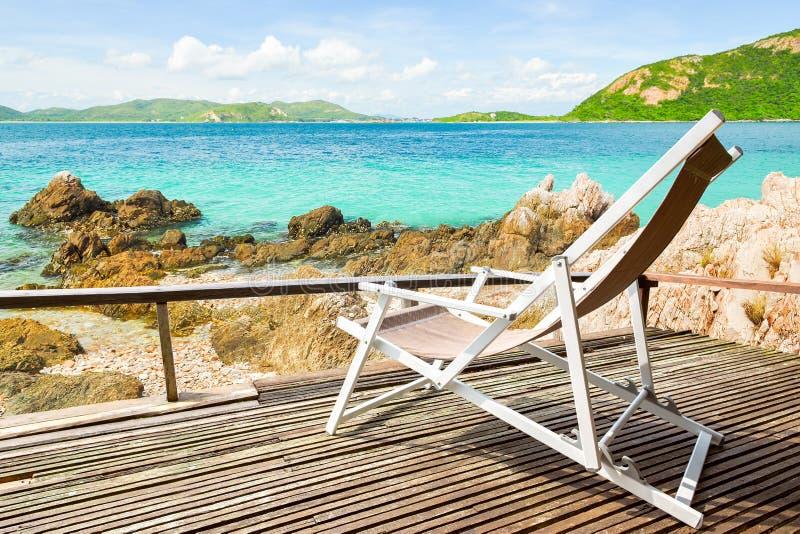Tropische Strandlandschaft mit Stühlen für Entspannung auf hölzernem te lizenzfreie stockfotografie