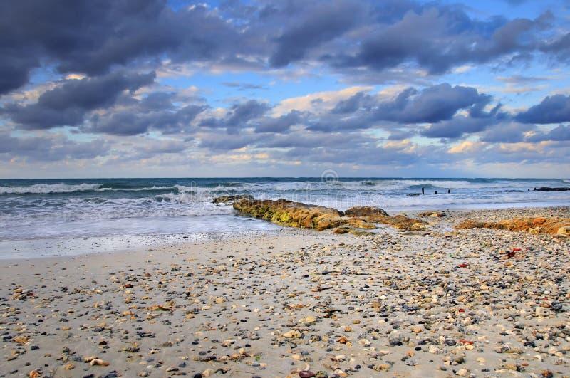 Tropische Strandszene mit bunten Wolken lizenzfreie stockfotos