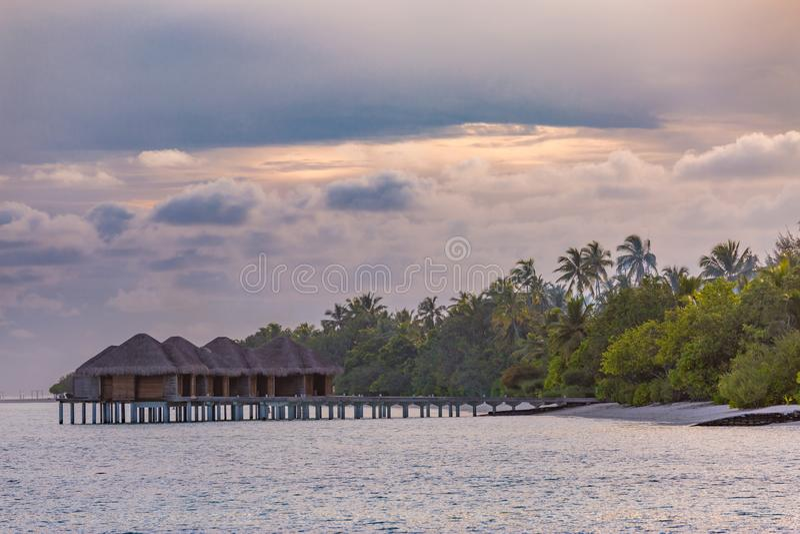 Tropische strandzonsondergang, watervilla's, luxetoevlucht met palmen en bewolkte hemel royalty-vrije stock fotografie