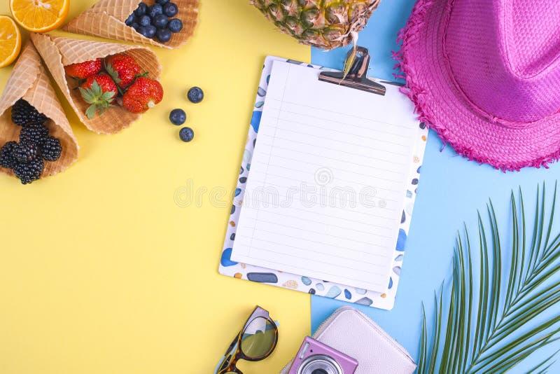 Tropische vruchten en bessen op een gele en blauwe achtergrond Toebehoren voor vakantie en ontspanning Witte raad met golvend stock foto's